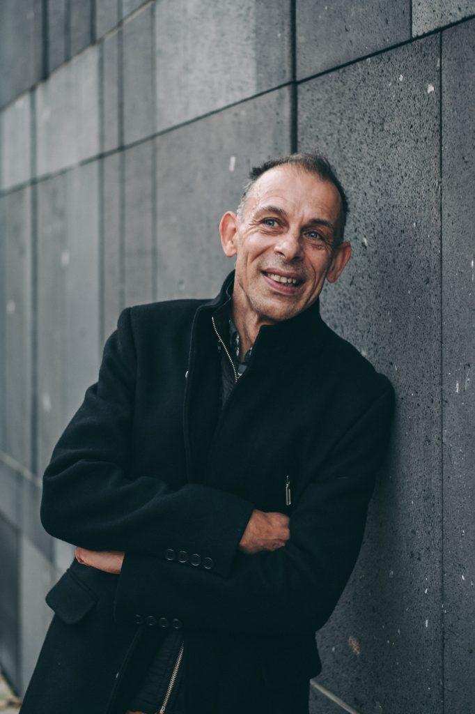 Foto von Josef Hochmeister, er lehnt an einer grauen Wand