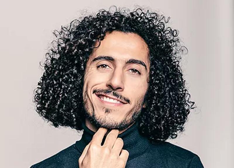 Foto: Omar in Rollkragenpullover. Er fast sich ans Kinn und lächelt